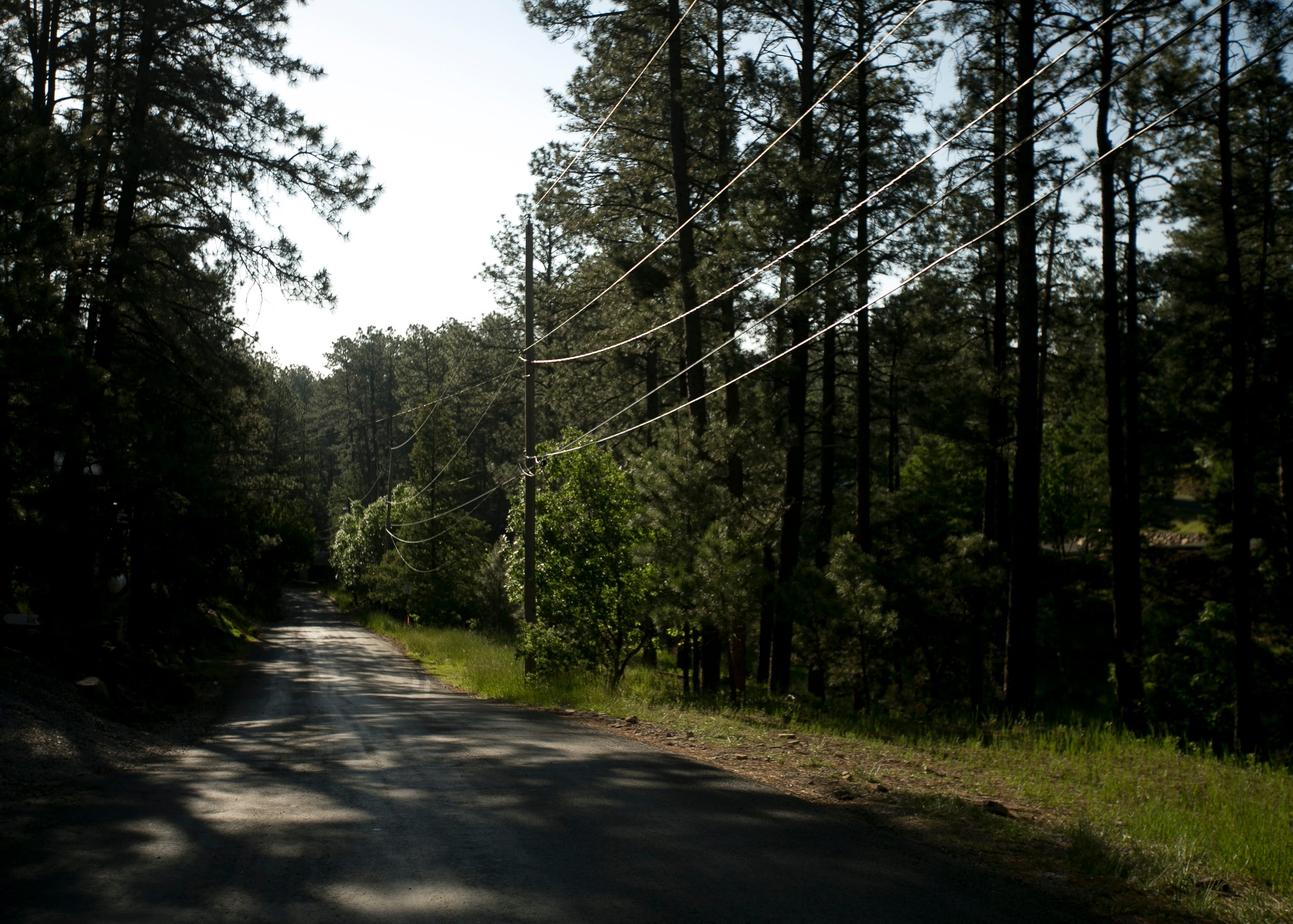 Power lines cut over a narrow one-way road in Upper Canyon in Ruidoso, New Mexico, on June 1, 2019.