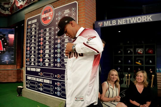 Brennan Malone, a right-handed pitcher from IMG Academy n Bradenton, Fla., puts on a jersey after being selected in the first round compensation round by the Arizona Diamondbacks in the Major League Baseball draft, Monday, June 3, 2019, in Secaucus, N.J.