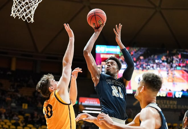 Feb 16, 2019; Laramie, WY, USA; Nevada Wolf Pack forward Jordan Brown (21) shoots against Wyoming Cowboys forward Hunter Thompson (10) during the second half at Arena-Auditorium.