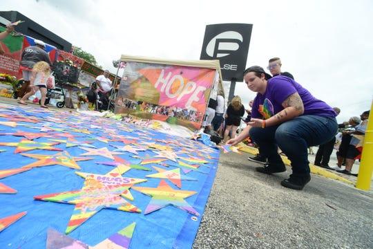 Personas colocan estrellas con mensajes escritos a las 49 personas que perdieron la vida en la matanza perpetrada hace 3 años en bar Pulse.