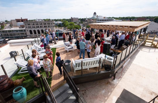 People gather on the roof of the Ballentine building during a ribbon cutting ceremony Wednesday, June 12, 2019 in Port Huron.