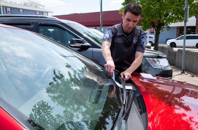 Port Huron Police Cadet Joseph Holzberger places a parking ticket on a vehicle Wednesday, June 12, 2019, in the Majestic lot in downtown Port Huron. Since the city began enforcing permit and 3-hour parking rules downtown, the number of tickets issued for violating those rules has increased drastically.