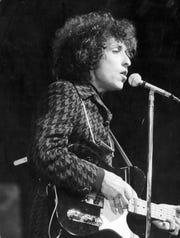 Profile view of American rock and folk musician Bob Dylan singing into a microphone and playing guitar during a concert at the Olympia music hall in Paris, France on May 1966. (Agence France Presse/Agence France Presse/Getty Images/TNS)