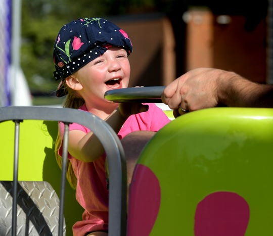 Stella Geesey, 3, of Manchester Township, takes a ride with her father Chris at the St. Joseph Carnival Tuesday, June 11, 2019. It is the 28th year for the Catholic church's annual carnival which runs through Saturday, June 15. Bill Kalina photo