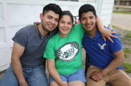 Paola, 28, sits with her brothers Gonzalo, 21, left, and Felix, 20, right, on a farm where the brothers work in western New York Sunday, June 9, 2019.  The trio were spending a Sunday afternoon together, that they all had off from working on a farm, before Paola moves out of the area to work on another farm.