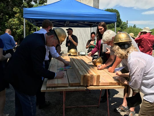 Oregon legislators join the public in signing wooden beams that will be used to build Habitat for Humanity houses