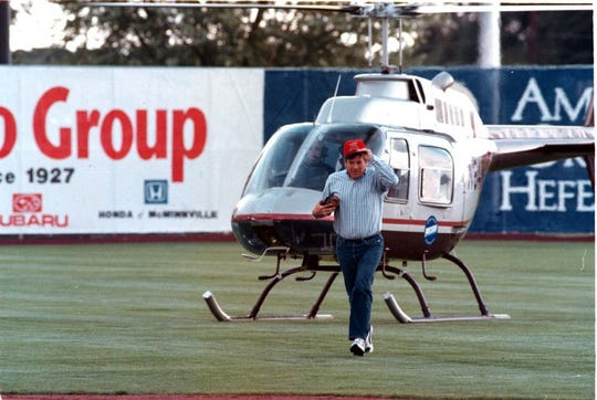 Keizer Mayor Dennis Koho pulls on his Volcanoes hat after arriving by helicopter to throw the first pitch of the minor league baseball team's inaugural season in 1997.