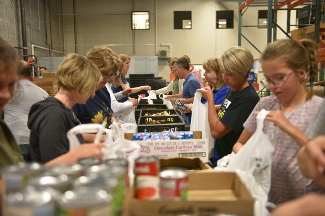 Members from Hillcrest Church load bags of food at Feeding South Dakota on Tuesday evening.