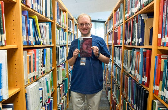 "Steven Prendergast stands in front of the autism resource section of the library Wednesday, June 12, in the Wegner Health Science Information Center where he is employed. Prendergast, who has autism himself, holds a book titled ""Born on a Different Planet"" about the experiences of people with autism."
