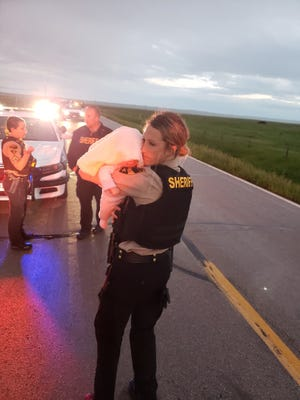 Deputy Kelsey Schwartz holds a baby following a pursuit on June 11, 2019.