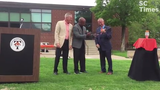 Superintendent Willie Jett gives a symbolic key to Mayor Dave Kleis to signify the upcoming transfer of Tech properties to the city to redevelop.