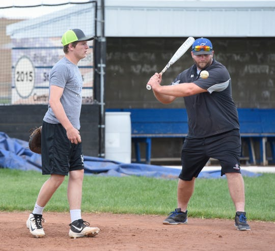 Mark Dierkes looks on from behind the plate as the team practices fielding Tuesday, June 11 at Foley High School.