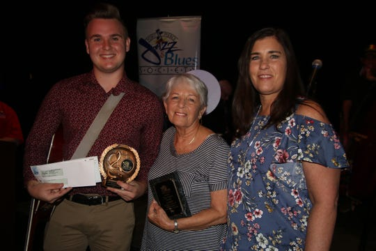 Tom Omans family members present the 10th annual Tom Omans Family Memorial Scholarship to alto saxophonist Christian Swierkowski, left, at the Fort Pierce Jazz & Blues Society 2019 Scholarship Awards Night.