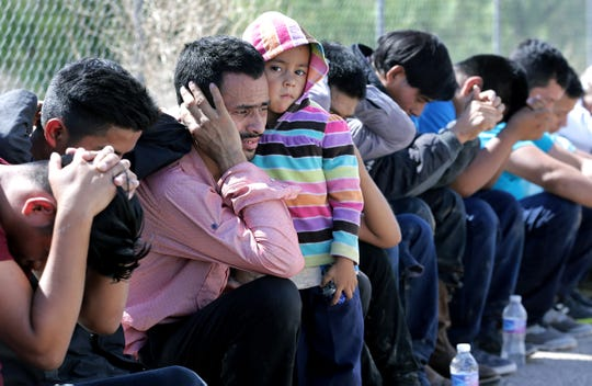 A young girl holds her father tightly as they are processed by Border Patrol after crossing from Juarez into El Paso Tuesday.