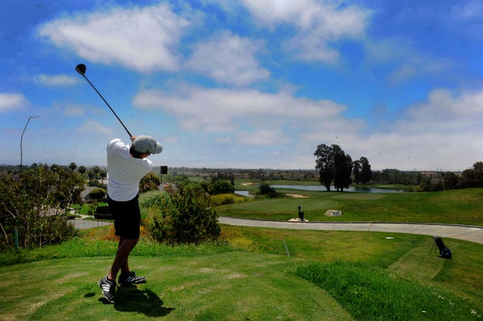 Golfer Robert Sierra whacks the ball from the top of the fourth hole at River Ridge Golf Club in Oxnard. The city of Oxnard will consider a proposal to bring in American Golf Corporation as the course's new operator.