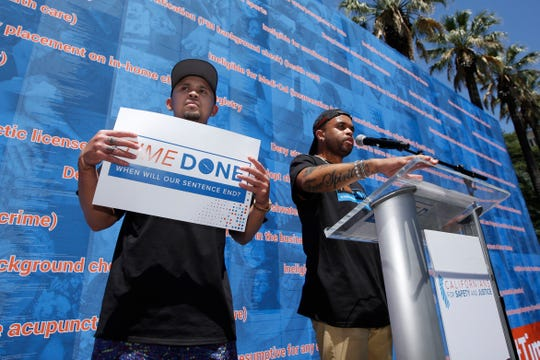Music artists P-Lo, left, and Bobby Brackins speak in support of legislation that would help automatically expunge old criminal records during rally at the Capitol in Sacramento.