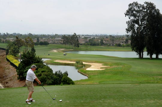 Johnny Alejo whacks the ball at the fourth hole at River Ridge Golf Club in Oxnard.