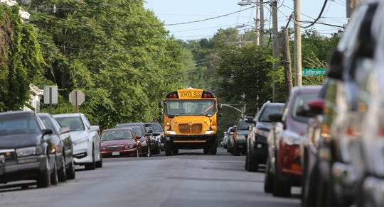 A school bus drives down 29th Street to pick up students.