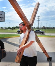Acie Burleson made a Wichita Falls pitstop Wednesday as he carries his large wooden cross across the United States spreading the word of God.