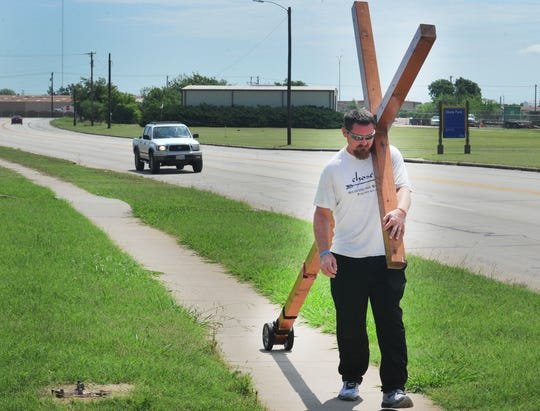 Acie Burleson carries his large wooden cross after making a pitstop Wednesday morning in Wichita Falls. Burleson said he is walking across the United States spreading God's word.