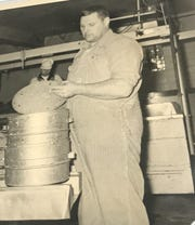 Leo Krohn (foreground) puts cheese in a press in the late 1950s.
