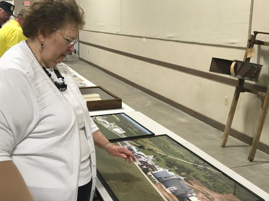 Jean Doell looks over some of the photos of the family's cheese plant Krohn Dairy as it evolved over the years.