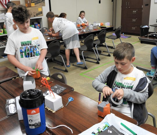 Jack Crook and Aiden Kesterson work on Orbots at Camp Invention at Coshocton Elementary School.
