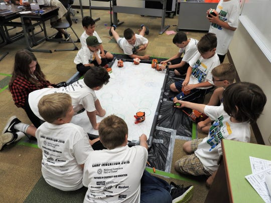 Students of Camp Invention at Coshocton Elementary School experiment with Orbots they made themselves. The challenge was to create a robot that could draw in various patterns to create artistic lines and circles.