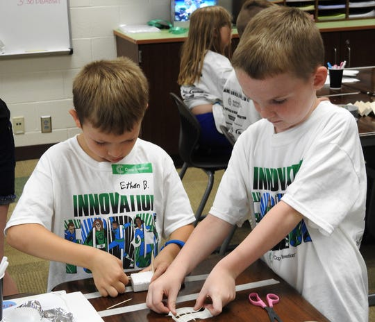 Ethan Byers and Will Snider work on a project in the Deep Sea Mystery unit of Camp Invention at Coshocton Elementary School. The project was to conceive a way to repair a boat and it transport you to a nearby island.