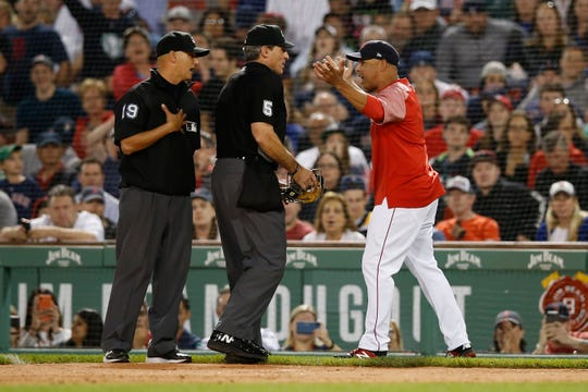 Boston Red Sox manager Alex Cora argues a call with umpires Angel Hernandez (5) and Vic Carapazza (19) during the fifth inning against the Texas Rangers at Fenway Park.