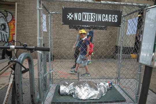 Riders leaving a MTA subway station in Dumbo, Brooklyn are greeted with a pop-up art installation promoting an immigration theme, Wednesday June 12, 2019, in Brooklyn, N.Y. Police officers responded around the city to display of cages bearing small mannequin representation of a child, a campaign called #NOKIDSINCAGES launched in support of the Texas based Refugee and Immigrant Center for Education and Legal Services. (AP Photo/Bebeto Matthews)