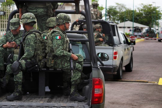 Mexican soldiers ride in the back of a pick up truck as they escort the caravan carrying Mexico's Minister of Defense, in Tapachula, Mexico, Tuesday, June 11, 2019. Mexican officials say they are beginning deployment of 6,000 National Guard troops for immigration enforcement, an accelerated commitment made as part of an agreement with the United States last week to head off threatened U.S. tariffs on imports from Mexico. (AP Photo/Marco Ugarte