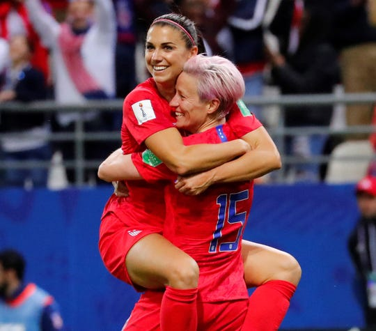 Alex Morgan (13) celebrates with  Megan Rapinoe (15) after scoring her fifth goal against Thailand during the Group F opener.