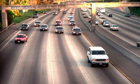 Police chase a Ford Bronco driven by Al Cowlings as he takes his friend, O.J. Simpson, to Simpson's home in Brentwood. The slow-moving June 17, 1994, freeway chase took law enforcement authorities through two counties after Simpson was charged with the murders.