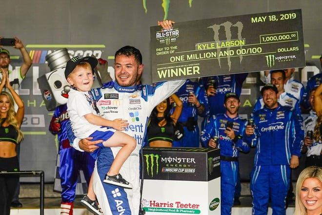 Monster Energy NASCAR Cup Series driver Kyle Larson (42) celebrates his win with his son Owen at the Monster Energy All-Star Race at Charlotte Motor Speedway.