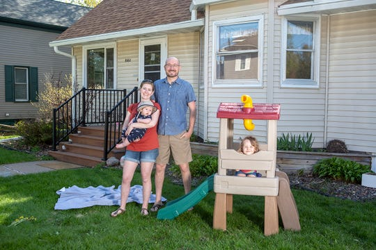 Karli-Rae and Christopher Kerrschneider play with their kids, Eleanor and Leviathan, in their front yard in Baldwin, Wis. (Ackerman + Gruber for Kaiser Health News)