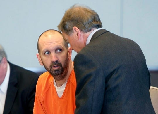 Craig Hicks, center, charged with the murder of three Muslim students in Chapel Hill, N.C., listens to with attorney Steve Freedman as he makes an appearance in a Durham County courtroom in Durham, N.C.