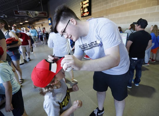 Caleb Gedemer signs the hat of Zeke Bartlett's hat, 7 of New London during the June 7 Timber Rattlers game at Fox Cities Stadium in Grand Chute.