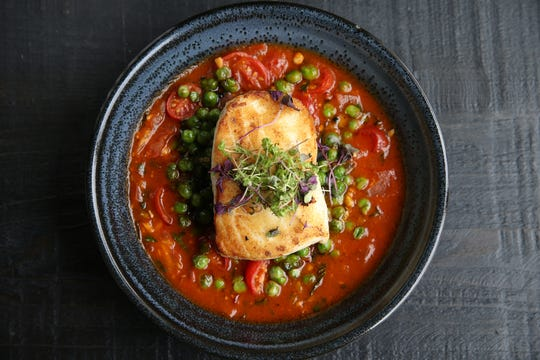Halibut with grape tomato broth, peas and mint at Iron Whale, Tim McLoone's newest restaurant on the boardwalk, in Asbury Park, NJ Thursday June 13, 2019.