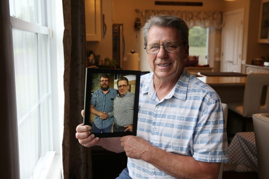 Michael Connallon, 72 of Hazlet, who recently learned of his 48-year-old son's existence through a DNA/ancestry search, holds a photograph of him and his son, John BuSha of New Bern, North Carolina.