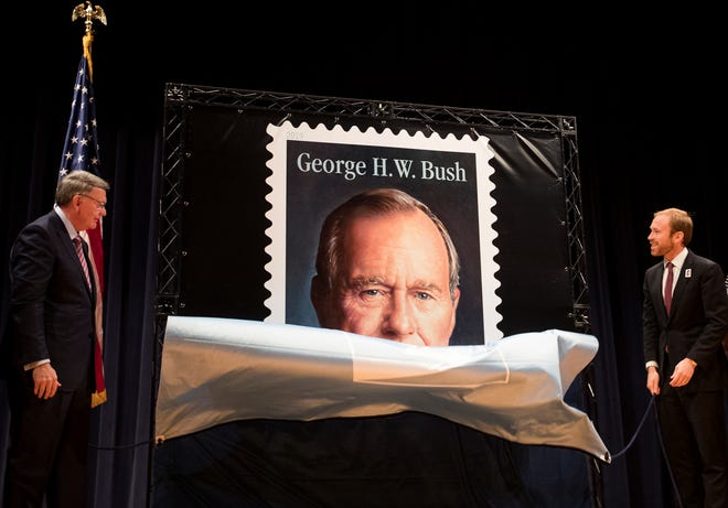 Robert Duncan, chairman, board of governors, United States Postal Service, left, and Pierce Bush, grandson of former President George H.W. Bush, unveil the Forever Stamp honoring former President George H.W. Bush on Wednesday, June 12, 2019, in College Station, Texas. The first-day-of-issue ceremony coincides with Bush's birthday. The Forever stamp features a portrait of the 41st president painted by award-winning artist Michael J. Deas. (Brett Coomer/Houston Chronicle via AP)