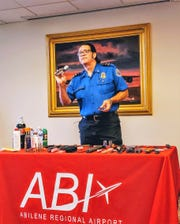 David Holbrook, a TSA supervisor at Abilene Regional Airport, holds up a boxcutter as part of a talk on prohibited items.