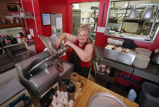 Betty Walker smiles as she slices bacon at her Sweet and Smokey Diner in Bremerton.