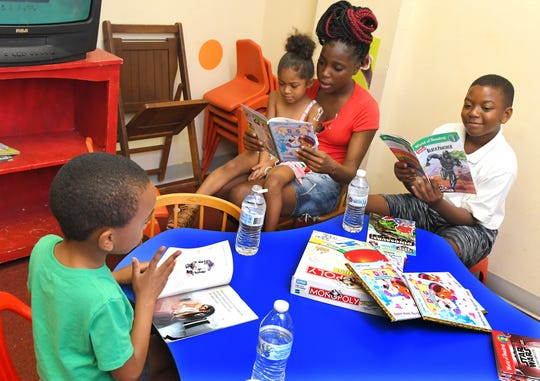The Community Youth Read and Feed program operates at three Brevard locations, including the Florida Avenue Church of Christ in Palm Bay, seen in this photo, at the border of south Melbourne. Volunteers prepare meals, read to the younger children, or provide books for the older kids. Left to right is Dylan Crump, Eva Daniels,  seated with volunteer Emoni McKenzie, and Tyshawn Campbell.