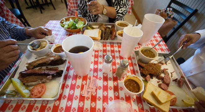 Customers eat lunch at Mike Cotten's BBQ in September 2015.