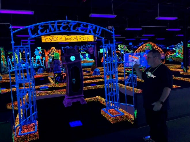 Pete Goodwin, one of three business  partners who opened Monster Mini Golf in Cherry Hill, shows off the unique monster-themed blacklight course.