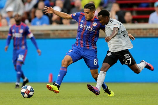 FC Cincinnati midfielder Victor Ulloa (8) battles for possession against Louisville City FC midfielder Napo Matsoso (27) in the first half of a US Open Cup match, Wednesday, June 12, 2019, at Nippert Stadium in Cincinnati.