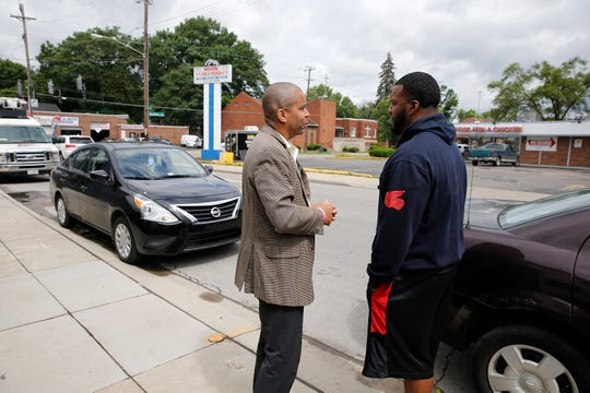 Vice Mayor Christopher Smitherman talks to Rico Middlebrooks, owner of Fat Bruh's food truck as Cincinnati Police investigate a shooting in the parking lot of Hook, Fish, and Chicken restaurant on the corner of  Reading Road at Dale Road in Bond Hill Thursday, June 13, 2019. Smitherman's office is across the street from the where the shooting took place but was not there when the shooting happened. A victim is a 37-year-old man with life-threatening injuries and was transported to University of Cincinnati Medical Center, police said.