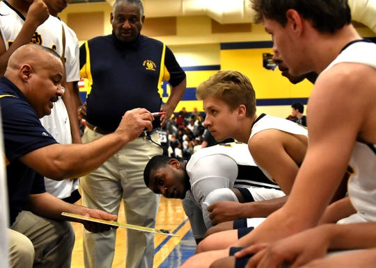 Walnut Hills Coach Ricardo Hill offers some third quarter instruction to his Eagles during a timeout, Jan. 19, 2018.