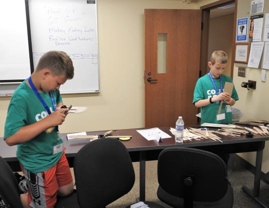 Gavin Locke and Kyle Roach work on wind turbines part of the Power Up and Go Green unit of College Aspire this week at Central Ohio Technical College's Coshocton Campus.